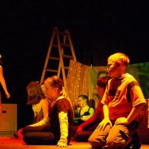 Dzieci siedzące w czasie występu teatralnego z gitarami