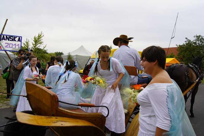 Młode panny z wiankami wysiadające z bryczki
